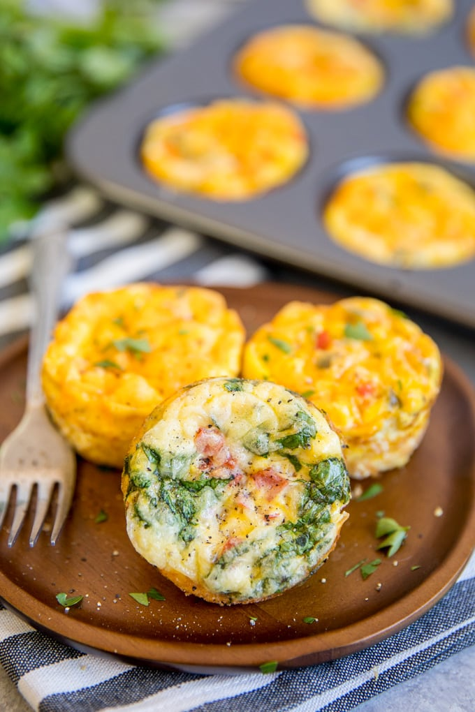 three different kinds of egg muffins on a plate with some in a muffin pan