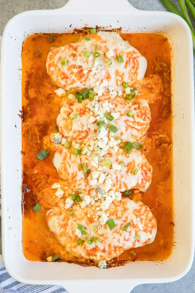 Four pieces of baked buffalo chicken in a large baking dish.
