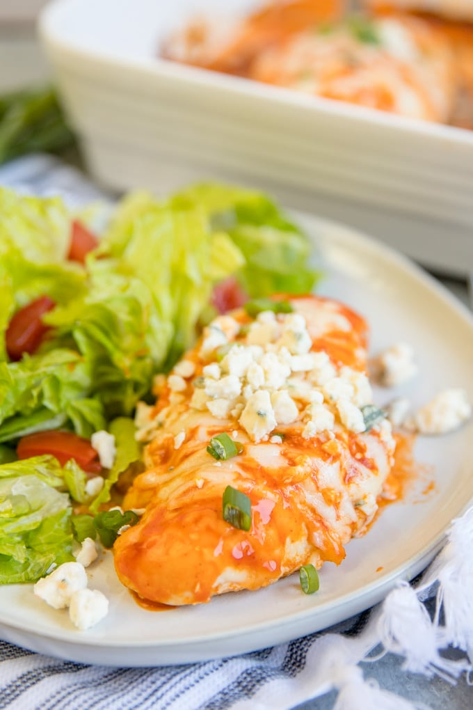 A piece of baked buffalo chicken on a plate next to a green salad.