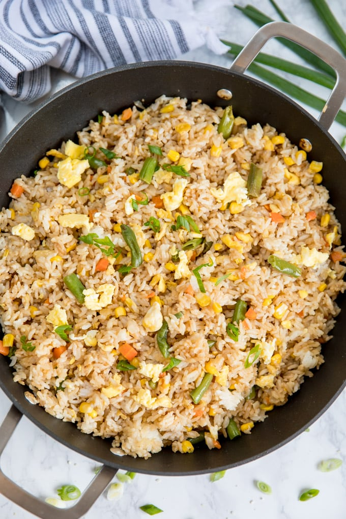 An over head shot of a skillet filled with egg fried rice.