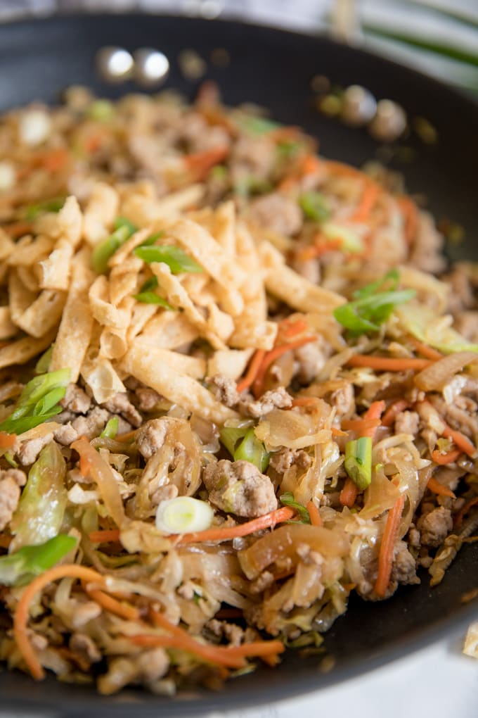 A close up of egg roll in a bowl in a large skillet with wonton strips.