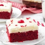 Red velvet brownie with cream cheese frosting on a white plate.