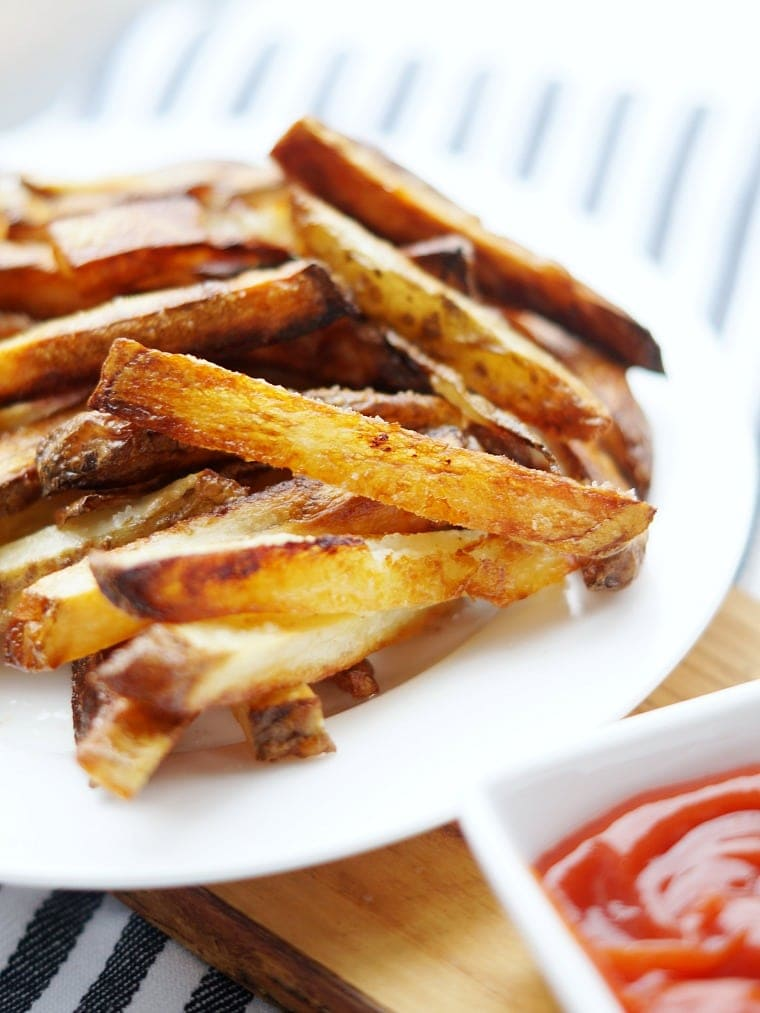 Close up of a plate of baked homemade french fries.