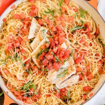 A pan filled with pasta and Bruschetta topped Chicken