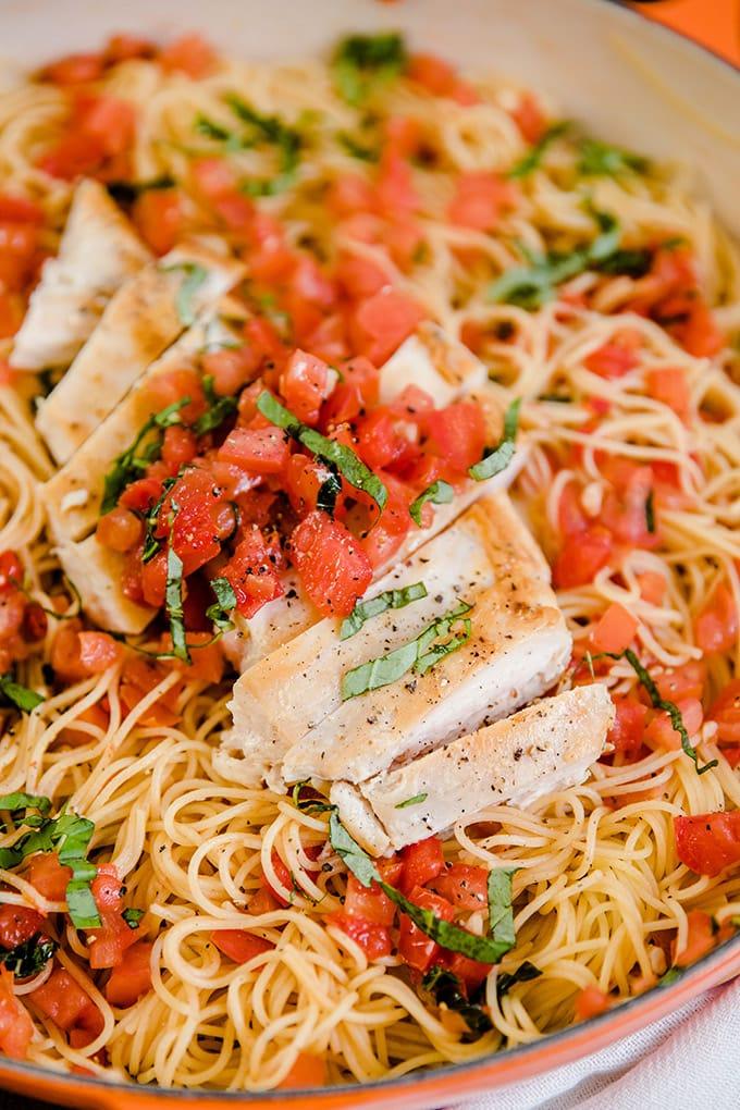 A close of of bruschetta chicken over pasta.