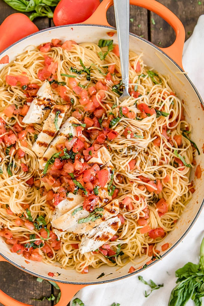 A pan of Bruschetta Chicken Pasta with a fork twirling pasta and a balsamic drizzle.