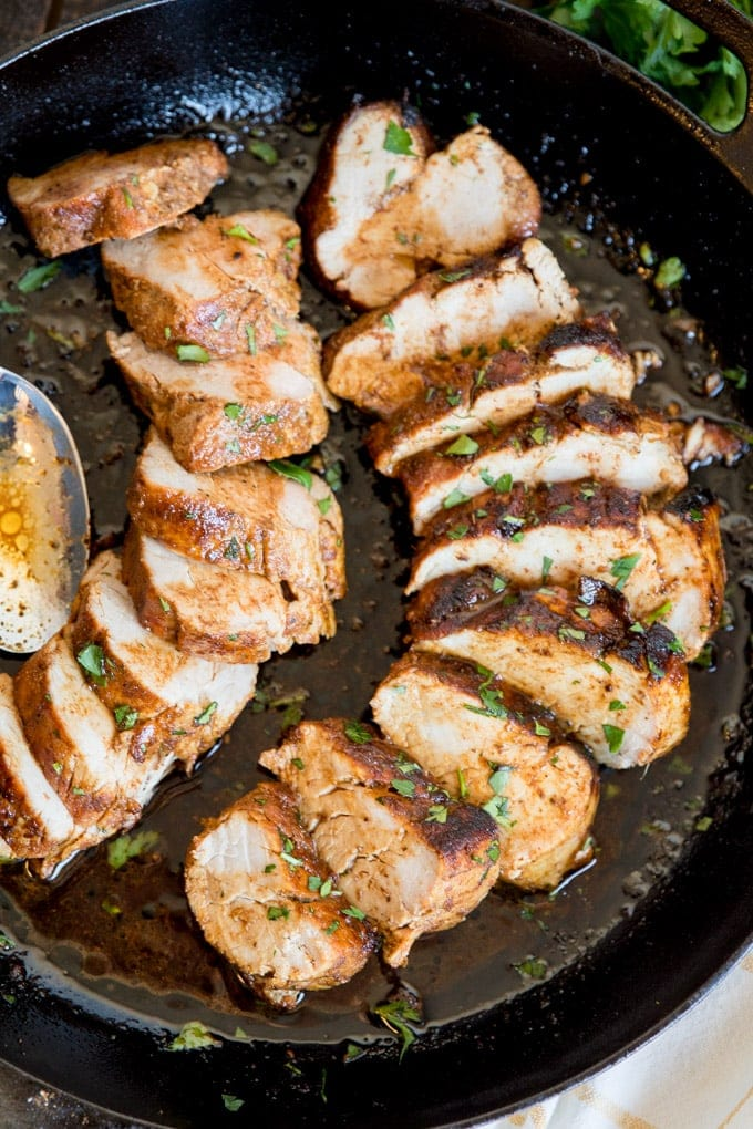 Sliced pork tenderloins in a cast iron skillet
