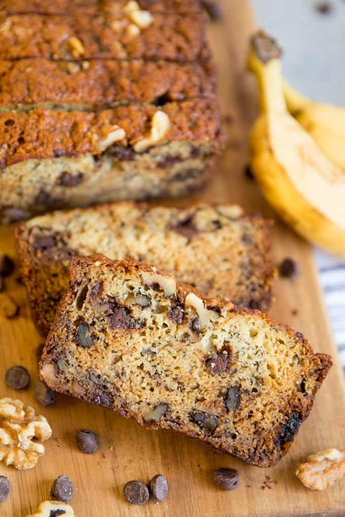A slice of chunky monkey banana bread surrounded by walnuts and chocolate chips.