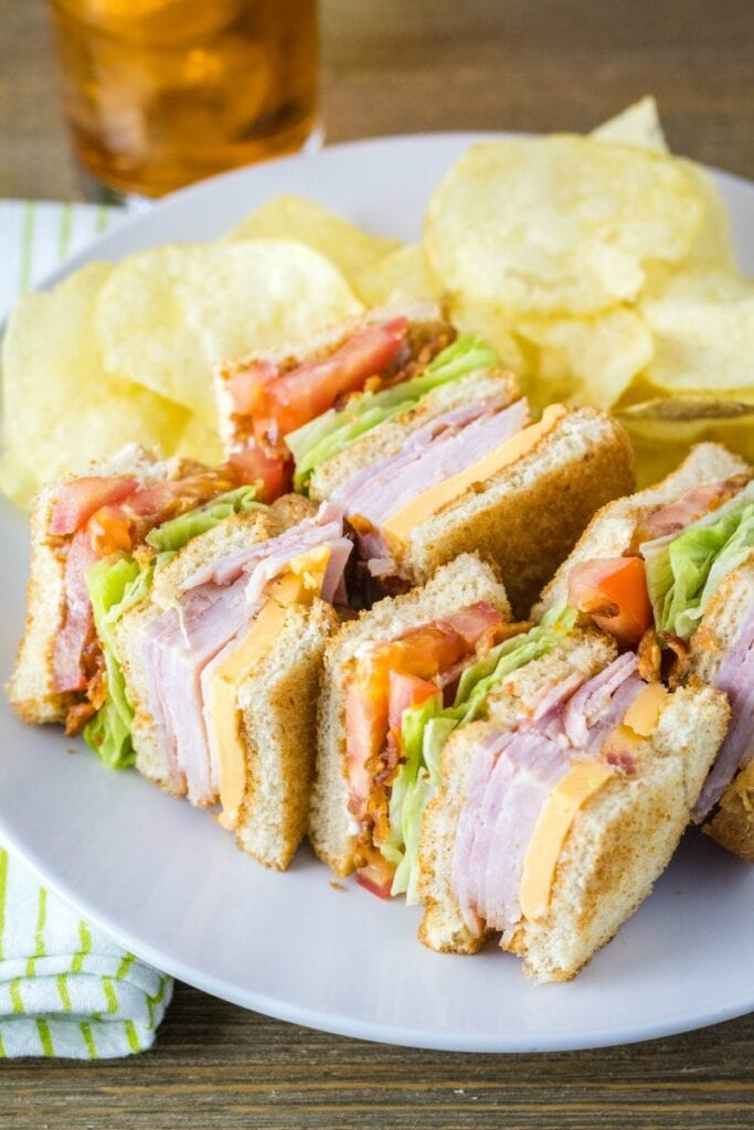 clube sandwich cut into quarters, laying down on a plate with chips