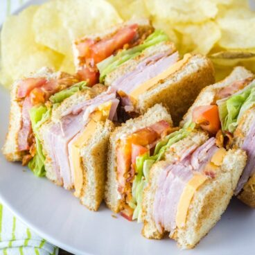 A club sandwich on a plate with chips