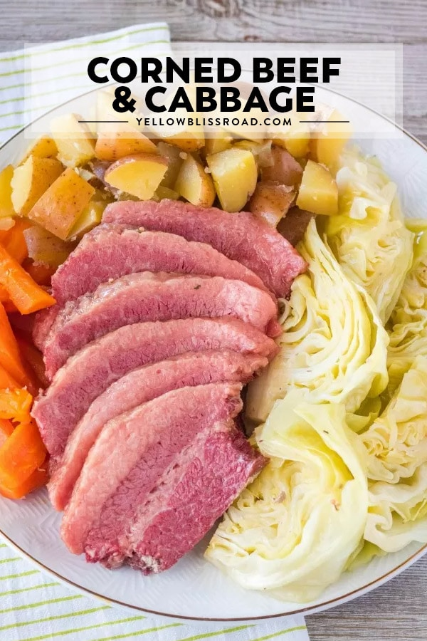 Corned Beef and Cabbage on a platter with potatoes and carrots. There is a title for the recipe on the image.