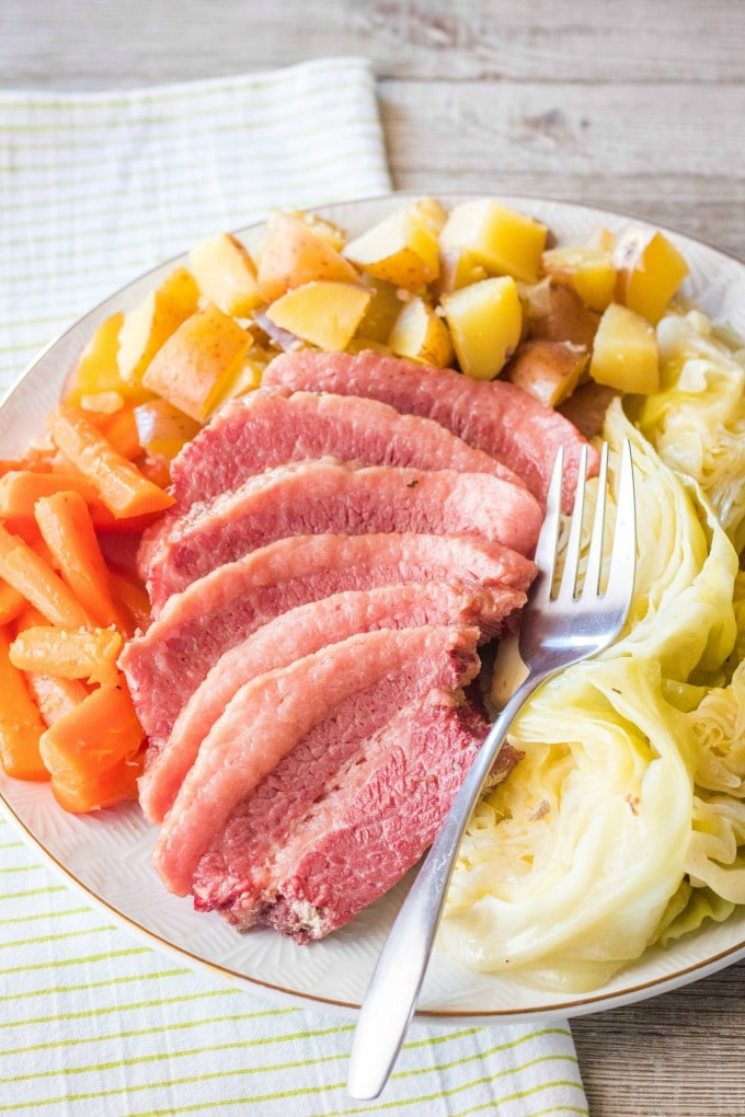 corned beef and cabbage recipe on a serving platter with a fork