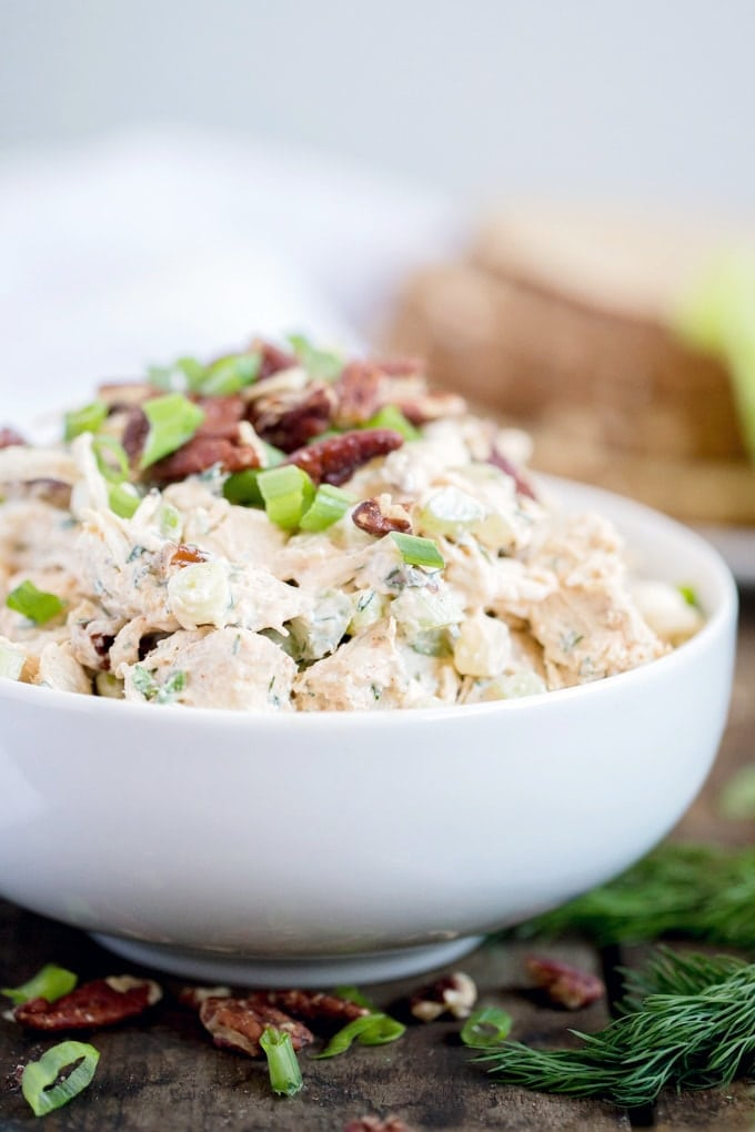 A bowl of chicken salad with dill and topped with pecans and green onions.
