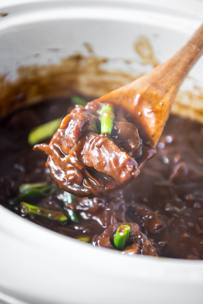 Slow Cooker Mongolian Beef on a wooden spoon.
