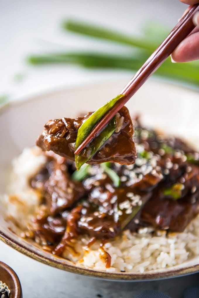 Slow Cooker Mongolian Beef held up with chopsticks