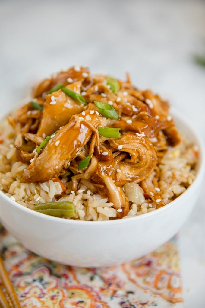Crock pot teriyaki chicken in a white bowl over a bed of fried rice.