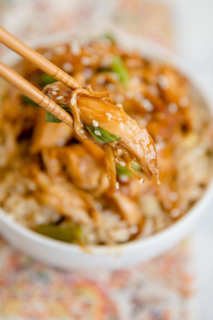 A piece of teriyaki chicken held between two chopsticks.