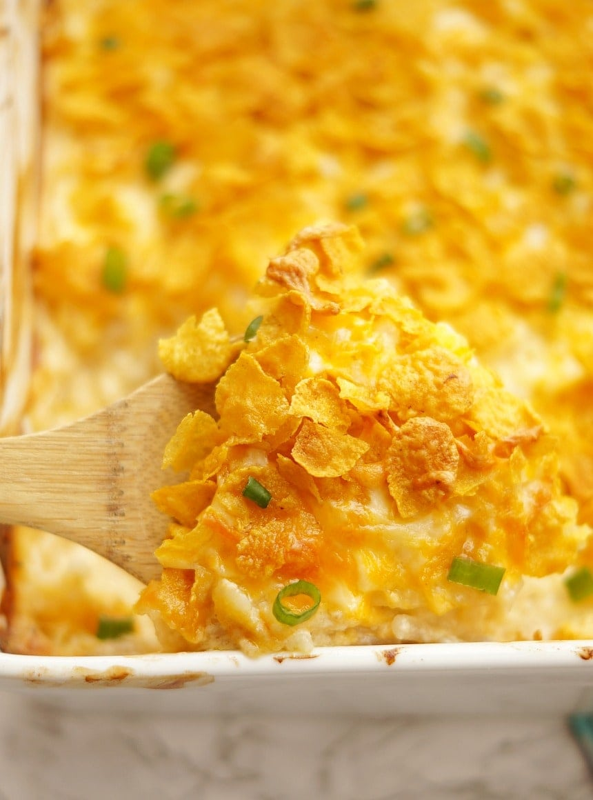 Cheesy Hashbrown Casserole serving on a wooden spoon