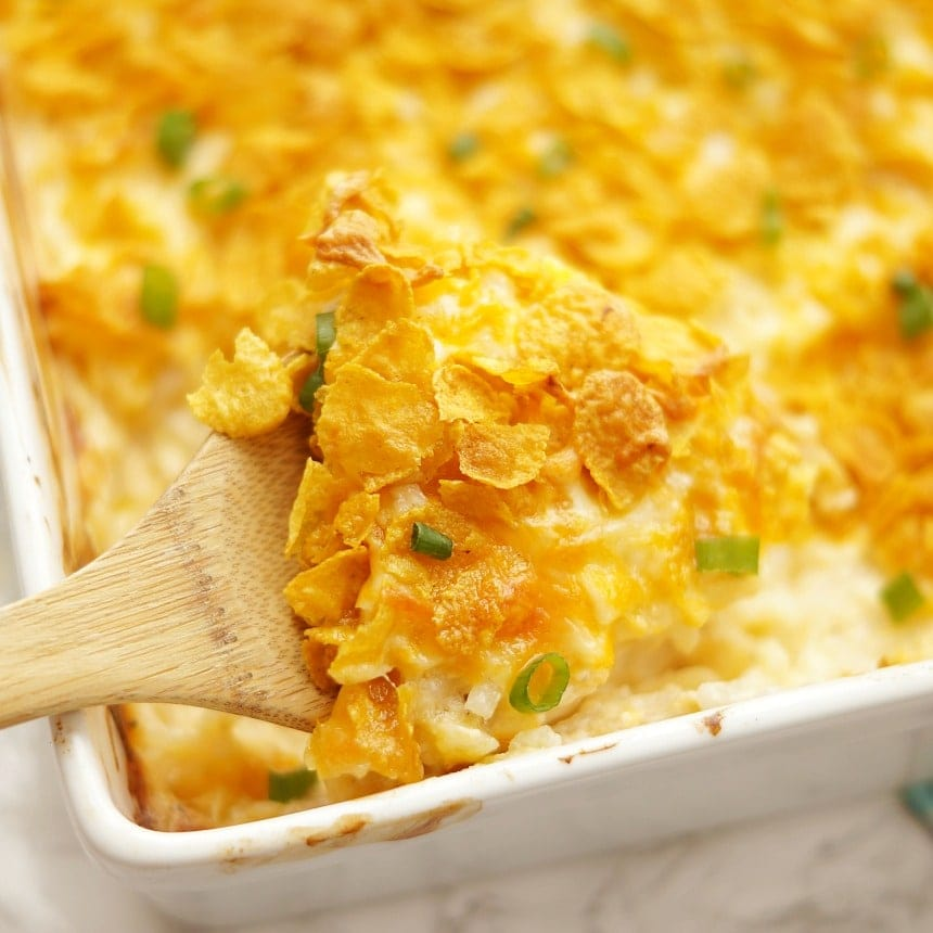 Cheesy Hashbrown Casserole with one serving lifted up on a wooden spoon.