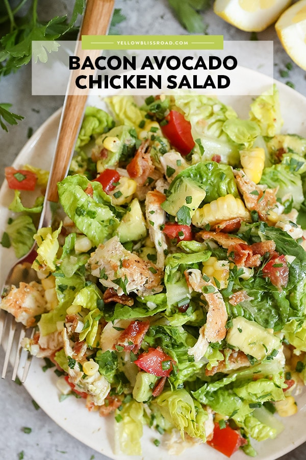 """Salad on a white plate, with lettuce, chicken, tomatoes, bacon and avocado. A wooden fork. Text reads \""""bacon avocado chicken salad\"""""""