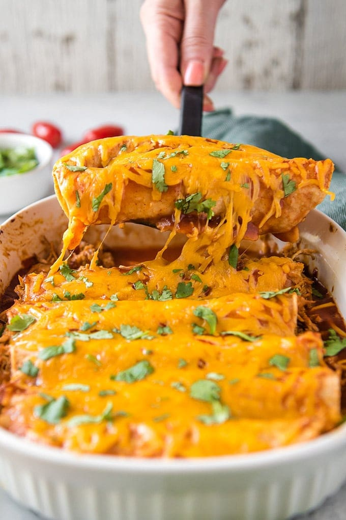 Chicken Enchiladas being lifted out of the pan with a spatula
