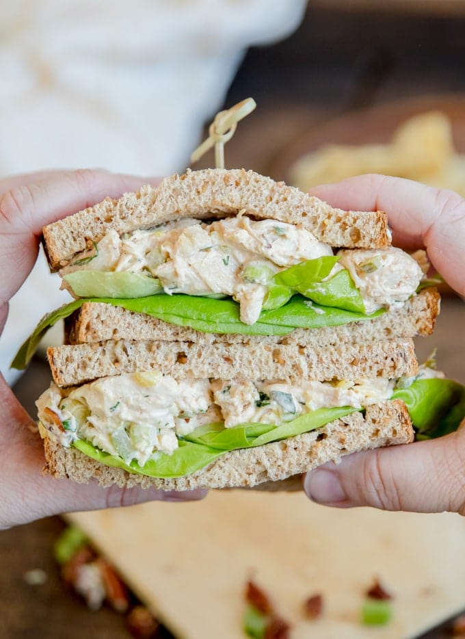 Hands holding two stacked halves of a chicken salad sandwich.