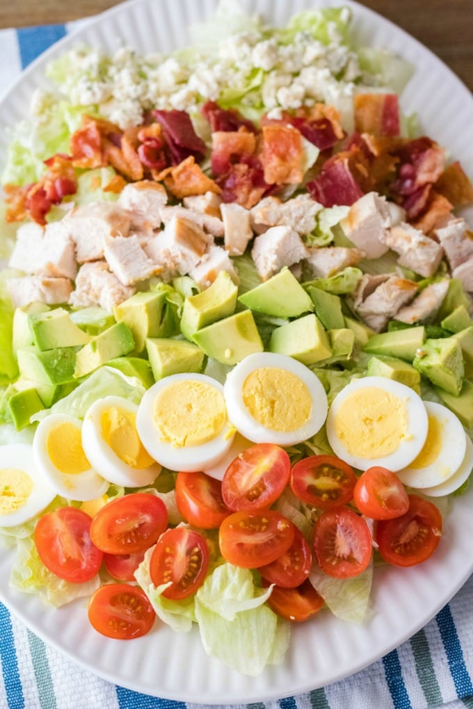 classic cobb salad with toppings lined up on top of lettuce