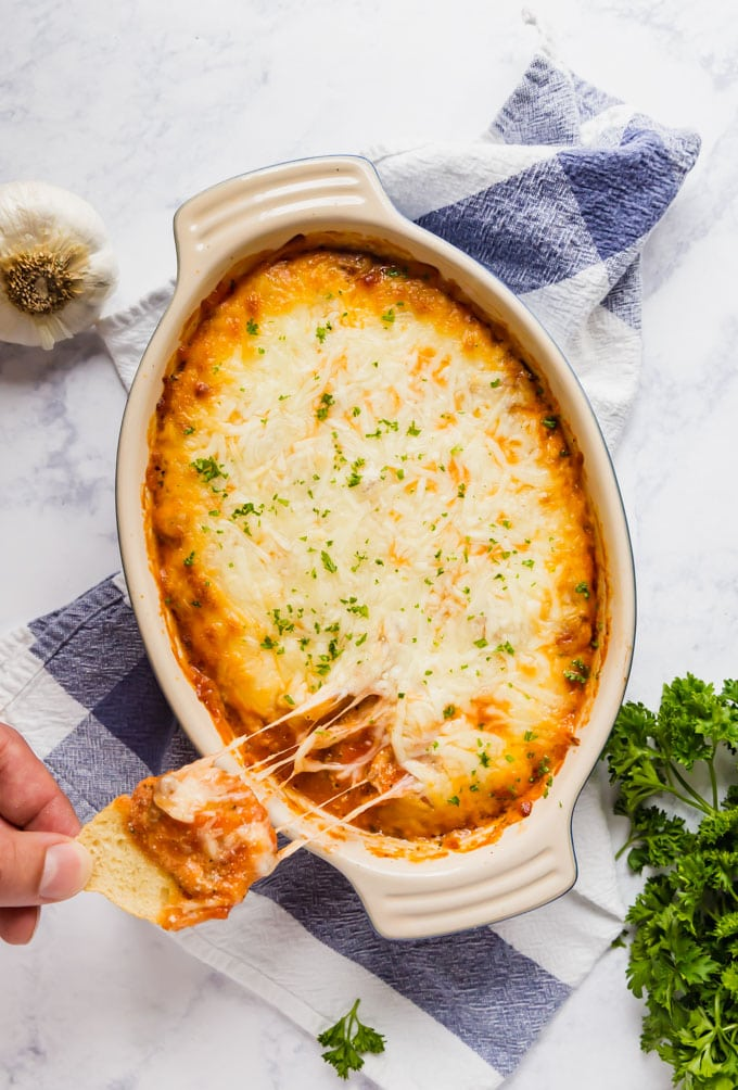 An overhead image of a dish of Lasagna dip with a hand taking some on a slice of baguette with melted cheese.