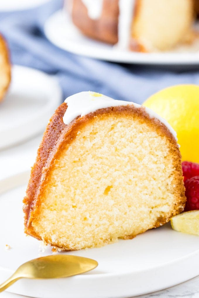 A slice of lemon pound cake with lemon glaze on a white plate.
