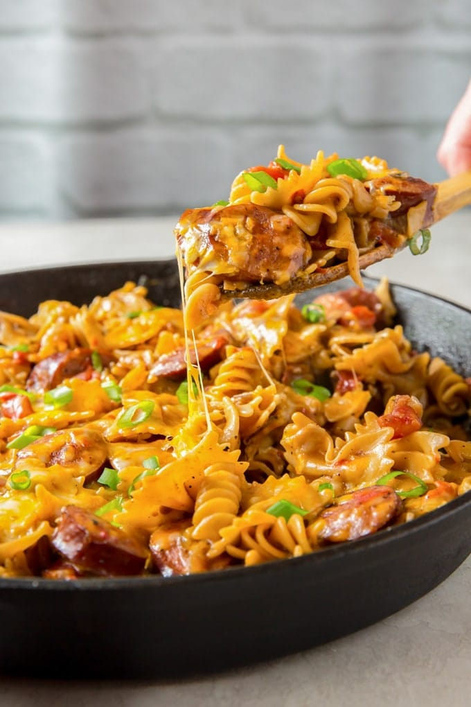 A skillet of cheesy smoked sausage pasta with a wooden spoon lifting a serving out of the skillet
