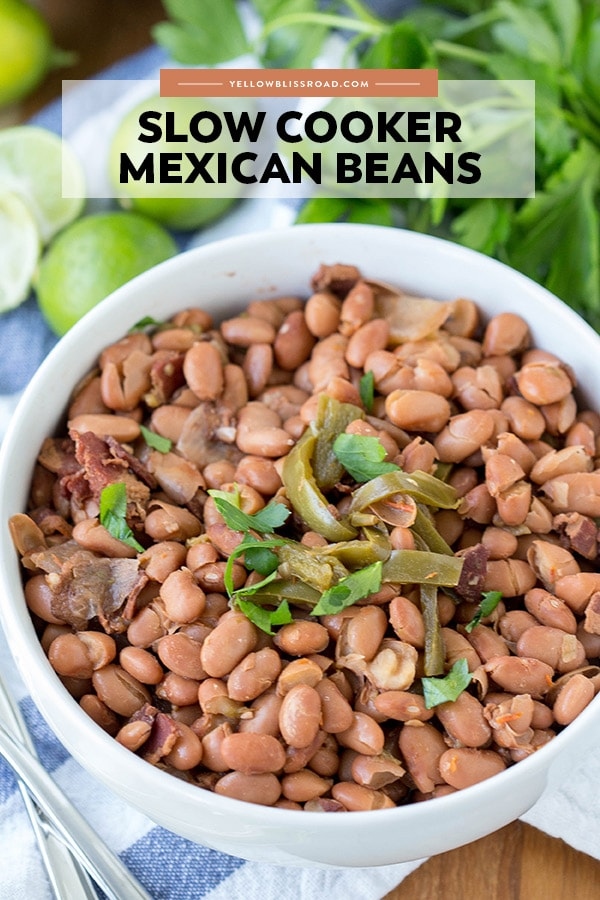 Mexican beans in a white bowl surrounded by limes and cilantro.