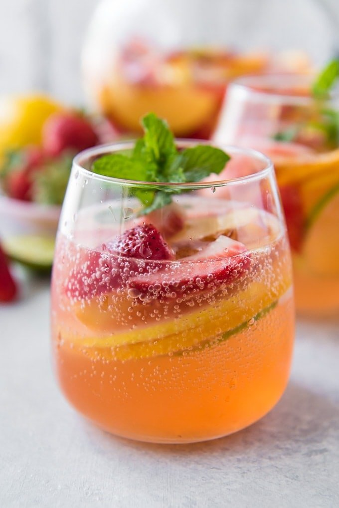 A close up of a glass of bubbling white sangria