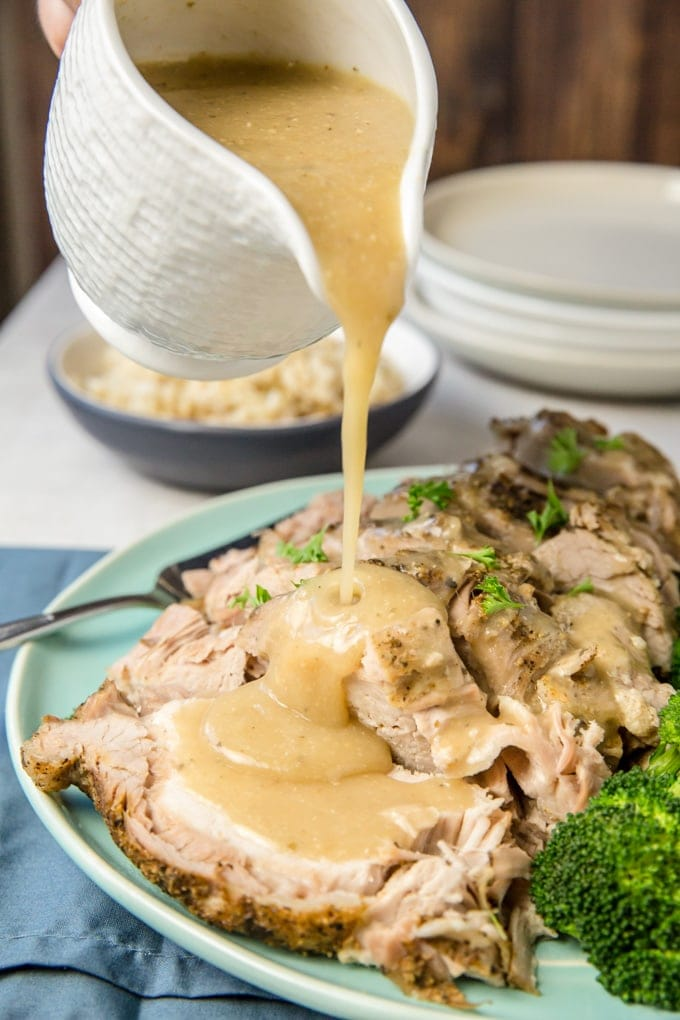 Crock Pot Pork Roast with gravy being poured on it.