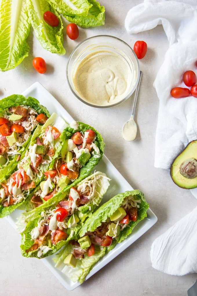 Chicken Club lettuce wraps on a plate, a bowl of dressing and tomatoes