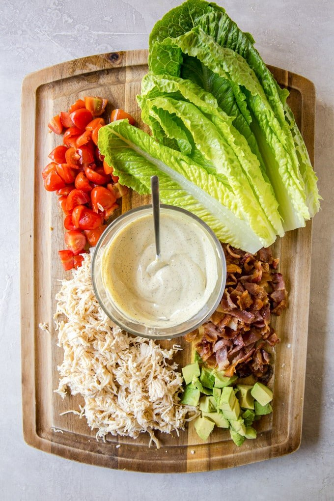 Ingredients to make lettuce wraps - Lettuce leaves, diced tomatoes, shredded chicken, bacon and avocado on a cutting board