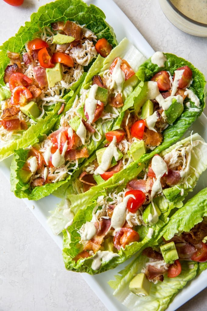 romaine lettuce cups with chicken, bacon, tomatoes and dressing.