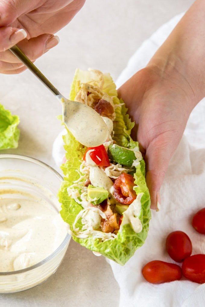 A hand holding a lettuce wrap and drizzling dressing on top