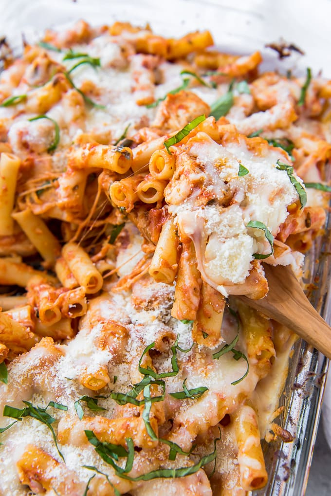 Baked Ziti on a wooden spoon sitting on a ziti casserole.