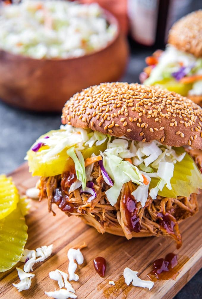 A bbq chicken sandwich topped with coleslaw and sliced pickles on a sesame seed bun