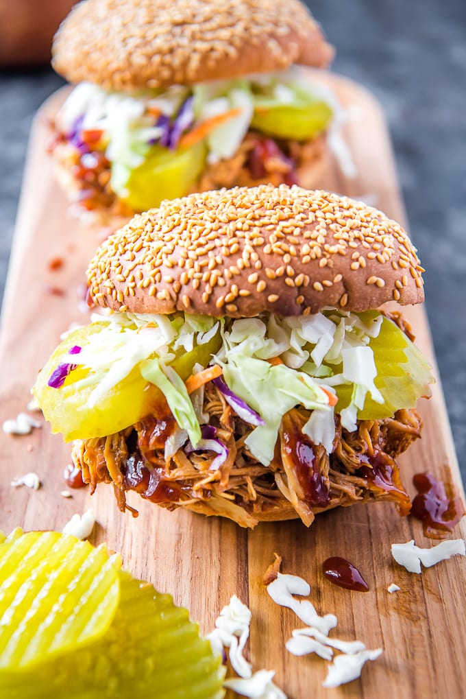 2 Crockpot BBQ Chicken piled onto sesame seed buns with coleslaw and pickles, sitting on a wooden cutting board.