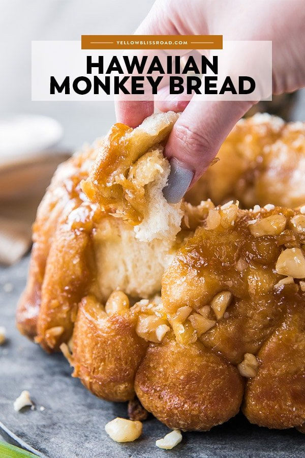 Hawaiian Monkey Bread with a hand taking a piece from it. Also with title text overlay.