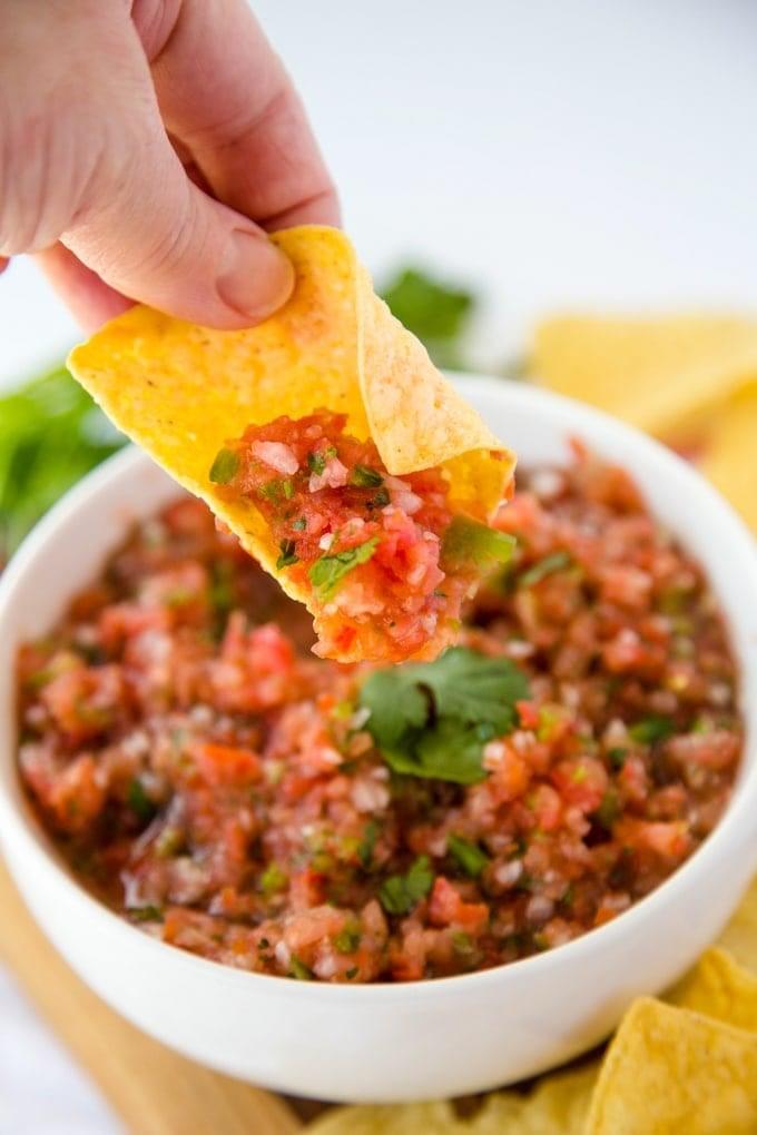 A tortilla chip dipped into fresh homemade salsa