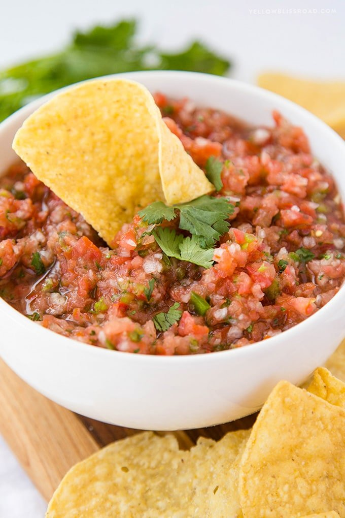 A bowl of homemade salsa with a tortilla chip in it
