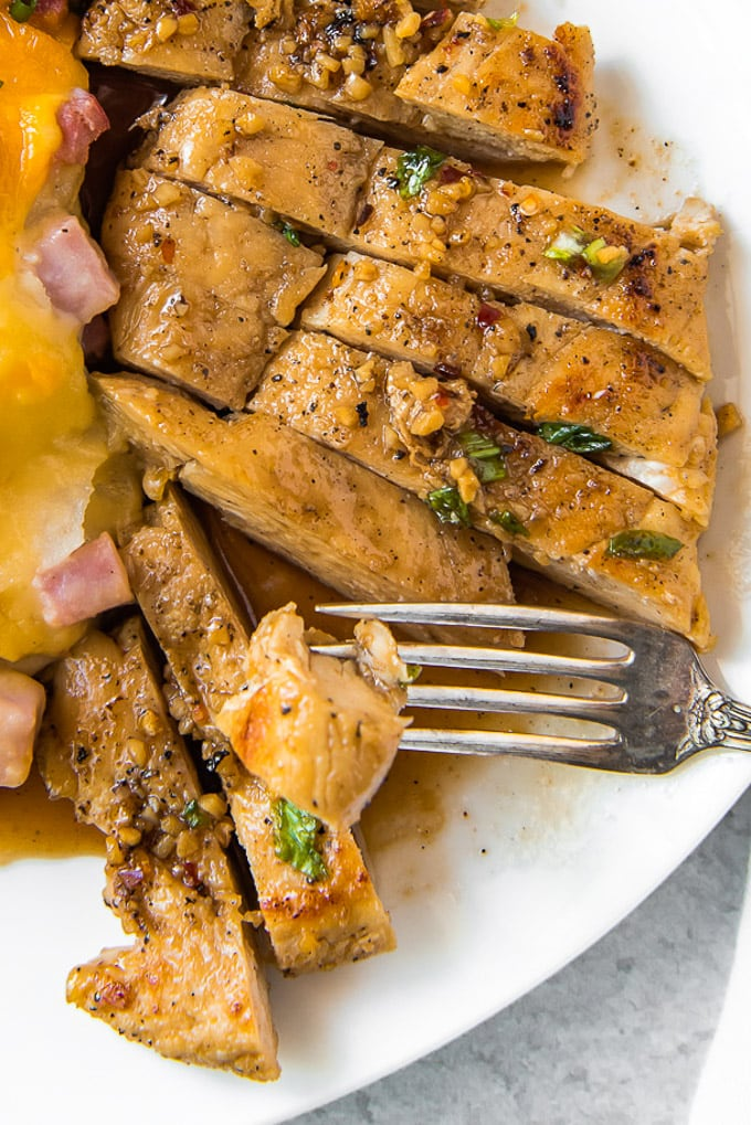 A sliced chicken breast with honey garlic sauce