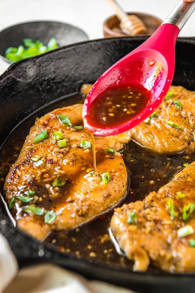 Honey garlic chicken in a skillet with sauce being poured on it.