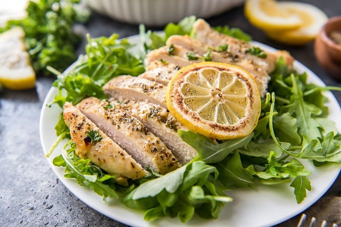 Lemon Pepper baked chicken sliced and sitting on a bed of arugula.
