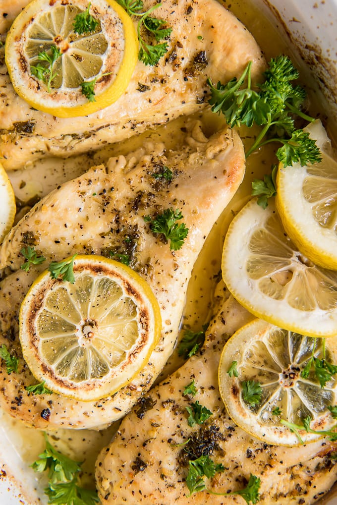 A close up of baked chicken breasts with lemon pepper seasoning and lemon slices.