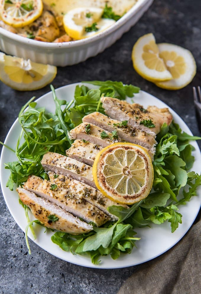 Sliced chicken on a bed of arugula on a white plate with lemon slices.
