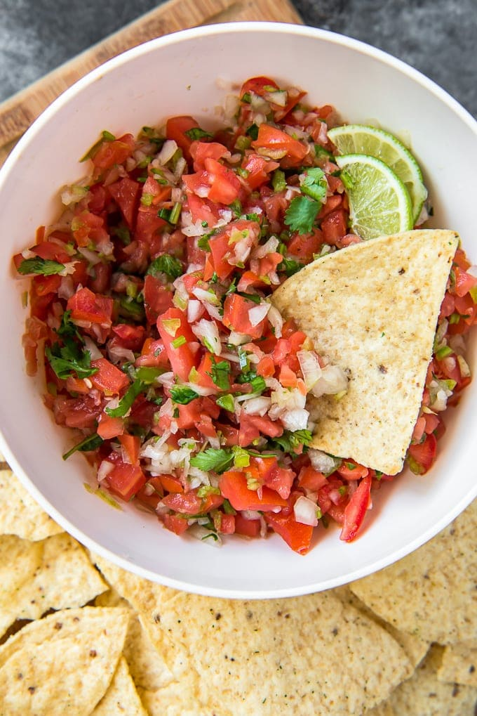 A large bowl filled with tomatoes, onions, jalapenos, cilantro and limes.