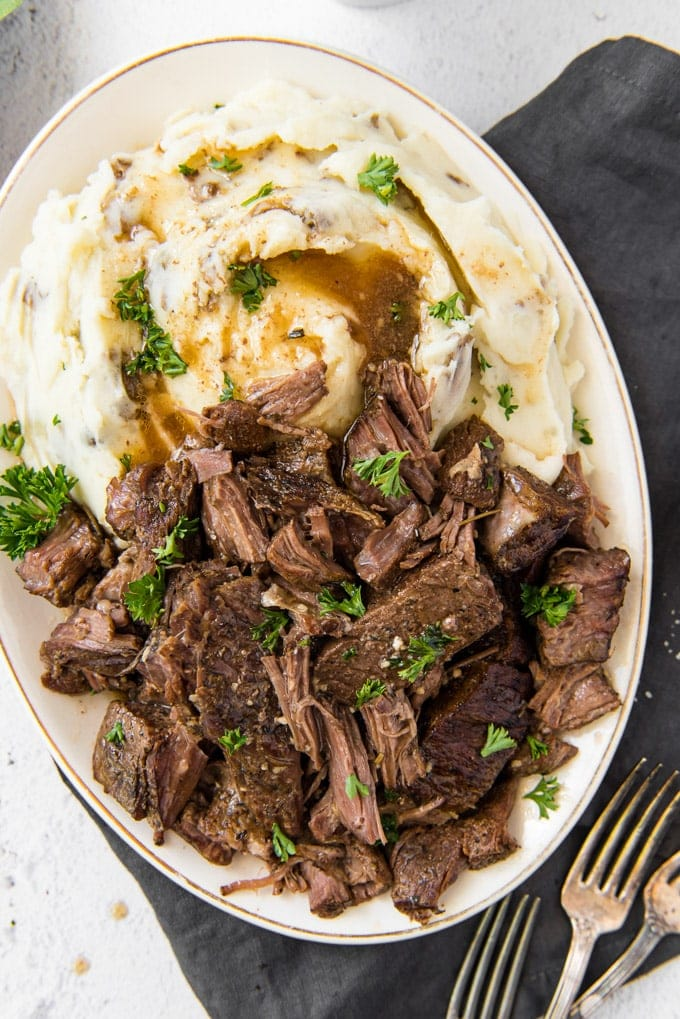 A platter of beef short ribs, slightly shredded, sitting next to mashed potatoes and gravy and sprinkled with parsley.